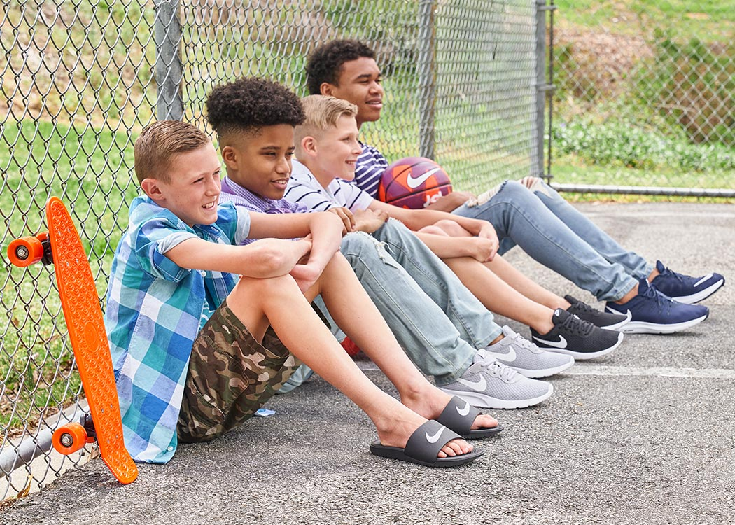 group of young men wearing nike slides and sneakers