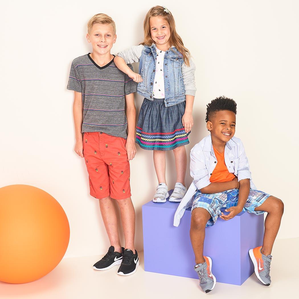 three cute kids wearing nike sneakers