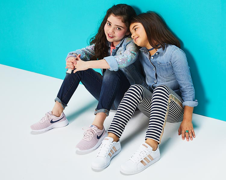 Two young girls one wearing pink nike sneakers and one wearing white and gold adidas sneakers.
