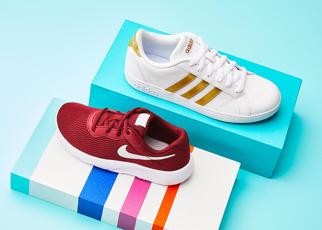 A red Nike shoe and a white and gold adidas shoe